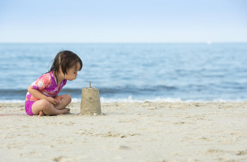 Little girl blowing on cake made with sand stock photo