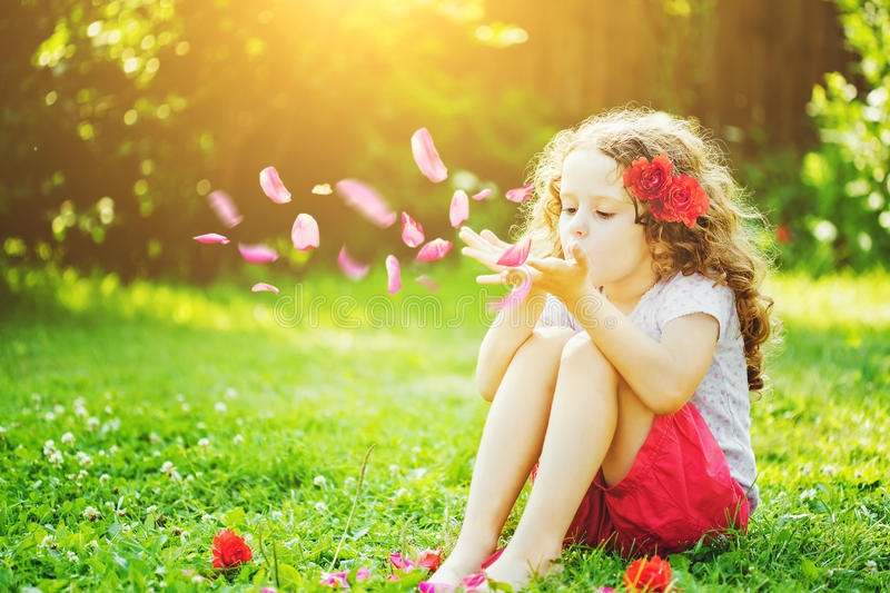 Little girl blowing flower petals from her hands in the sunlight stock photos