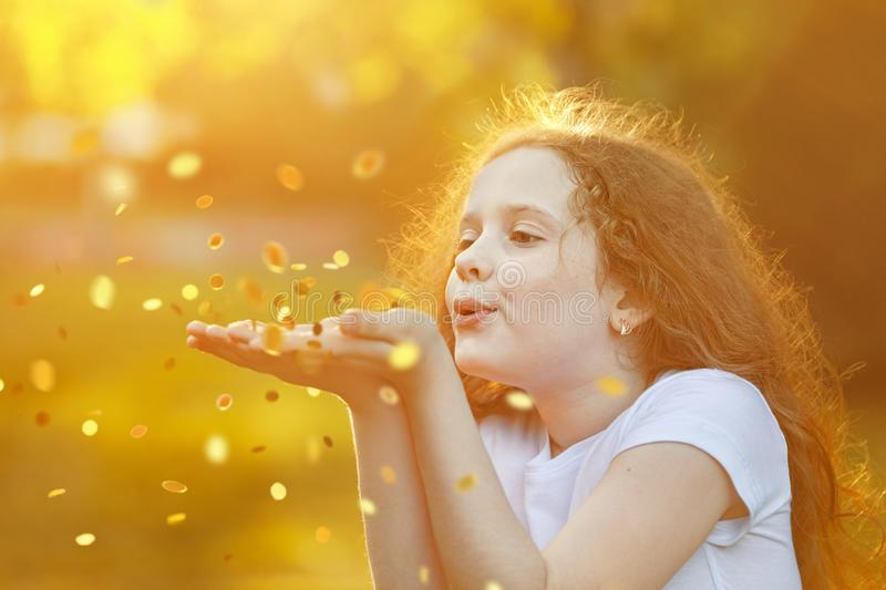 Little girl blowing gold confetti with her hand stock photo