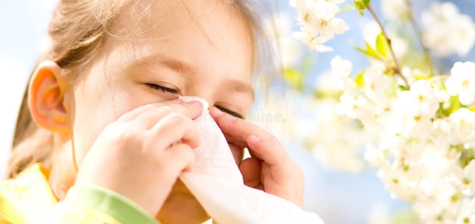 Little girl is blowing her nose. Near spring tree in bloom royalty free stock image