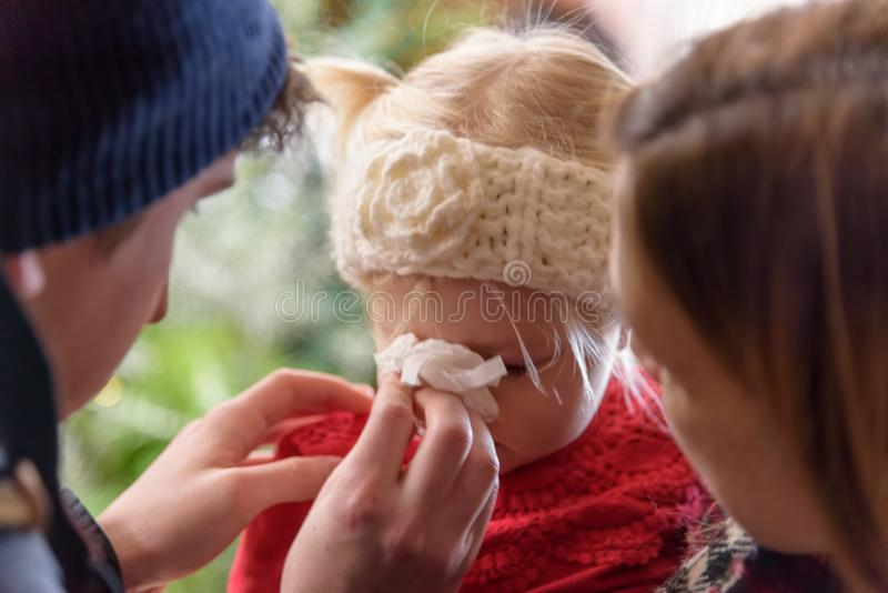 Little girl blowing her nose in tissue stock photo