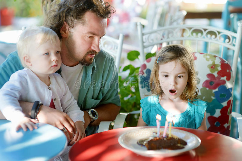 Little girl blowing out candles in her birthday royalty free stock photos
