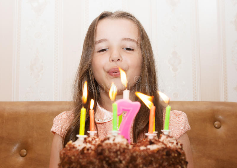 Little girl blowing out the candles stock image