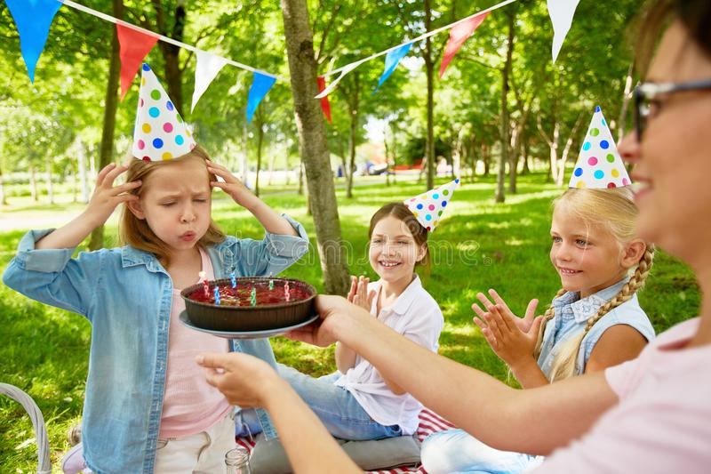 Sixth birthday. Little girl blowing six candles on birthday cake held by young women during summer picnic on weekend stock image