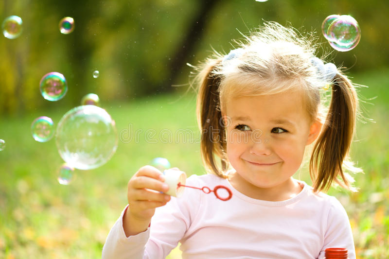 Little girl is blowing a soap bubbles stock image