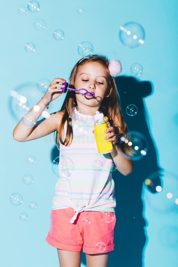 Little girl blowing soap bubbles on a blue background. royalty free stock photo
