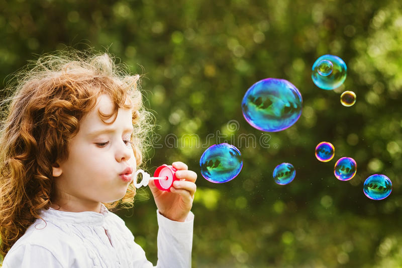 A little girl blowing soap bubbles, closeup portrait beautiful c. Little girl blowing soap bubbles, closeup portrait beautiful curly baby royalty free stock image