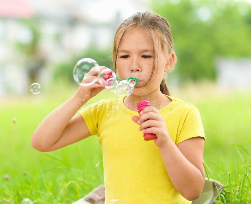 Little girl is blowing a soap bubbles. Cute little girl is blowing a soap bubbles stock image