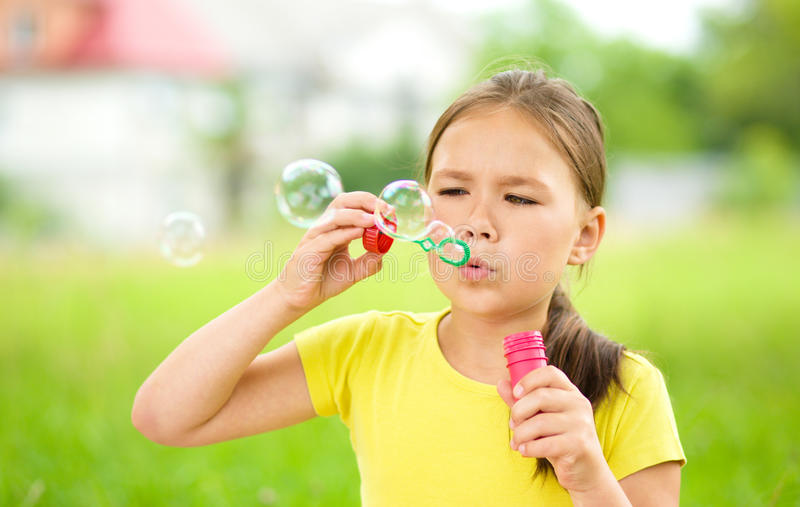 Little girl is blowing a soap bubbles. Cute little girl is blowing a soap bubbles royalty free stock photography