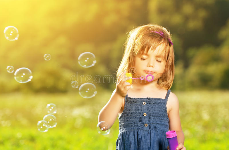 Little girl blowing soap bubbles in nature royalty free stock photos