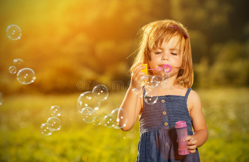 Little girl blowing soap bubbles in nature royalty free stock photo