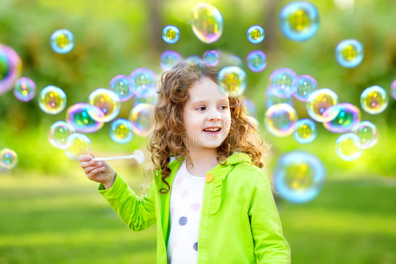 A little girl blowing soap bubbles stock image