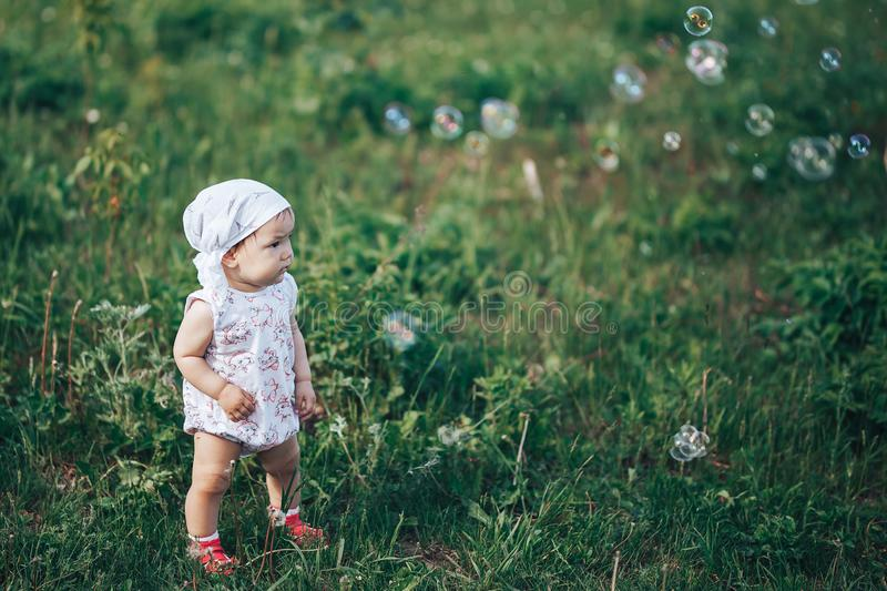 A little girl blowing soap bubbles, spring portrait beautiful one year old kid.  stock images