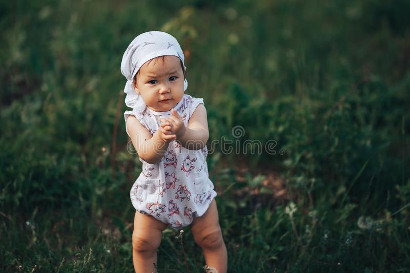 A little girl blowing soap bubbles, spring portrait beautiful one year old kid.  royalty free stock photo