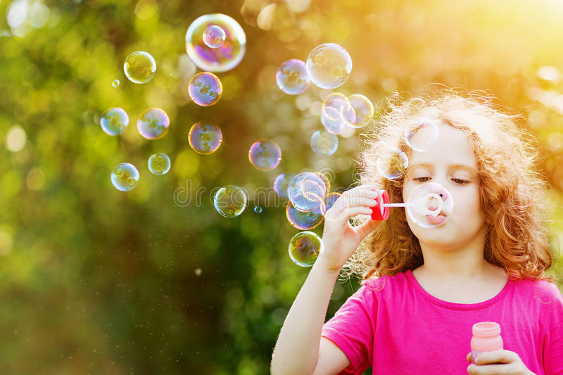 A Little Girl Blowing Soap Bubbles In Summer Park