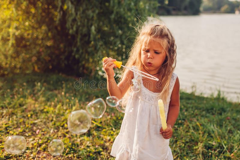 Little girl blowing soap bubbles in summer park. Child having fun stock photo