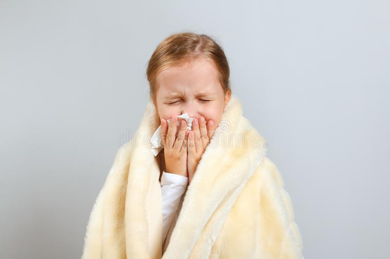 Little girl blows her nose, wrapped in a plaid, on a gray background stock photos