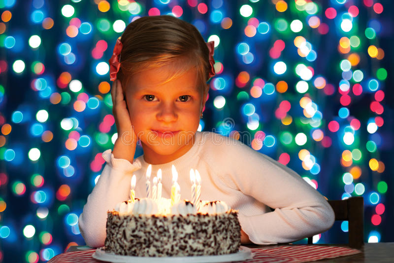 Little girl blows out the candles on the cake royalty free stock photos