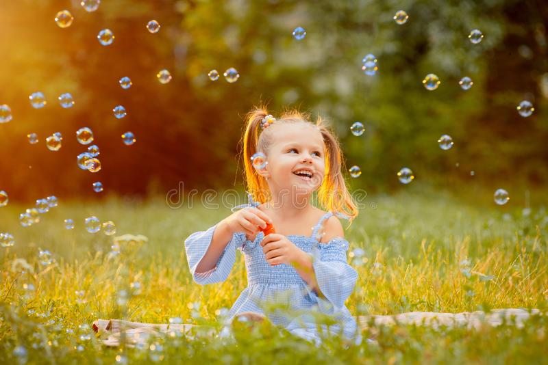 A little girl blows soap bubbles stock images