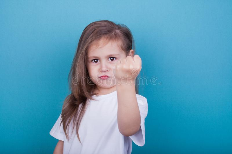A little girl threatens with a fist stock photos