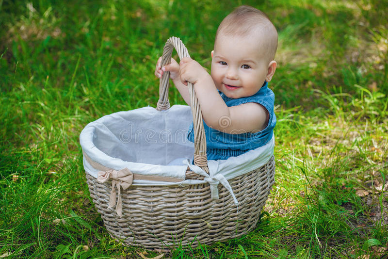 Little girl with a blue bow on her head sitting in wicker, white basket, sunny day in the park royalty free stock images