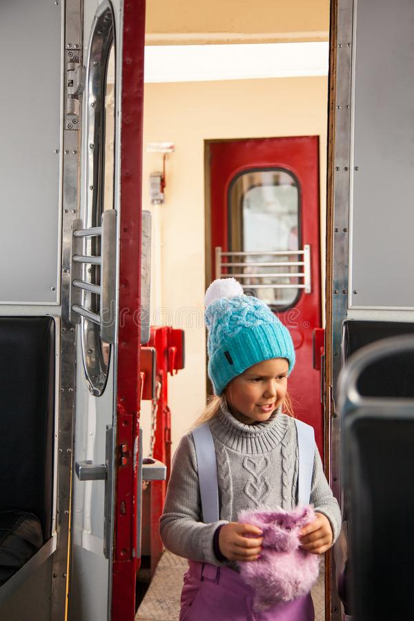 Little girl in blue cap and winter pants tarvelling by old train Kukushka in Georgia between Bakuriani and Borjomi royalty free stock photography