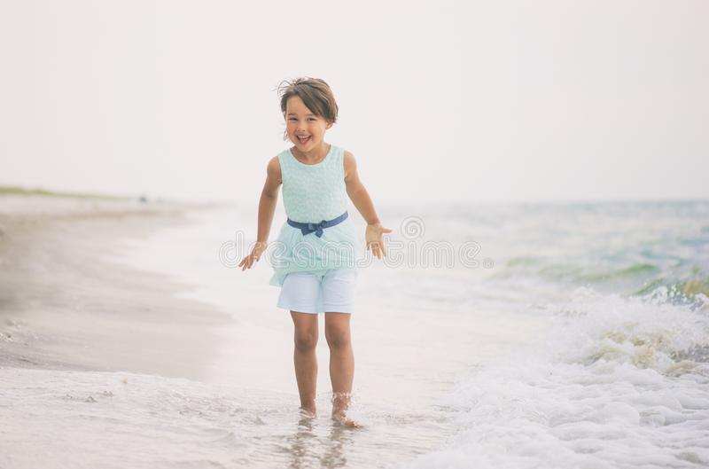 Little girl with blue dress having fun in sea water royalty free stock photo