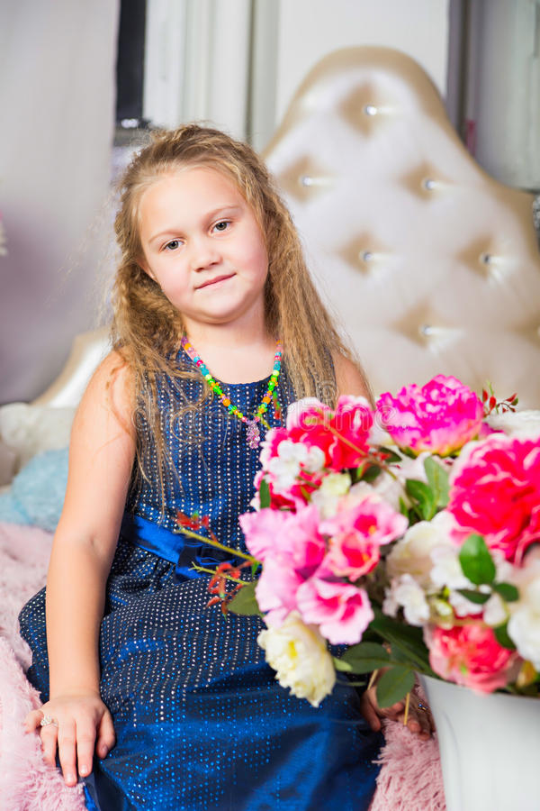 Little girl in blue dress sitting on the couch stock photo
