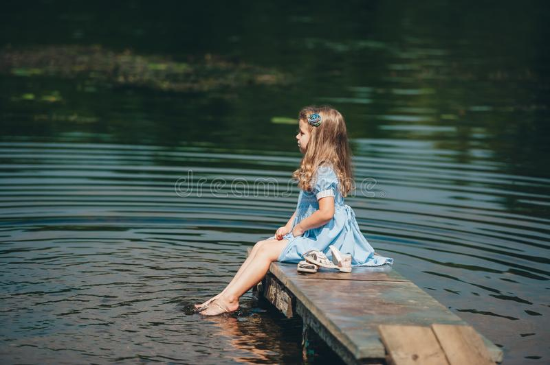 Little girl in blue dress sitting on a wooden pier near the water. Kid alone on the river. Side view. Little girl in blue dress sitting on a wooden pier near the stock photography