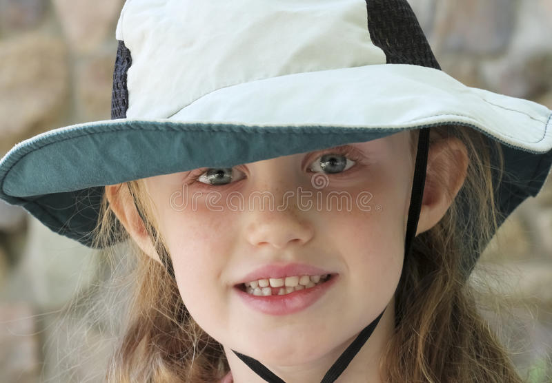 A Little Girl with Blue Eyes and a Floppy Sun Hat. A Portrait of a Little Girl with Big Blue Eyes and a Floppy Sun Hat stock photos