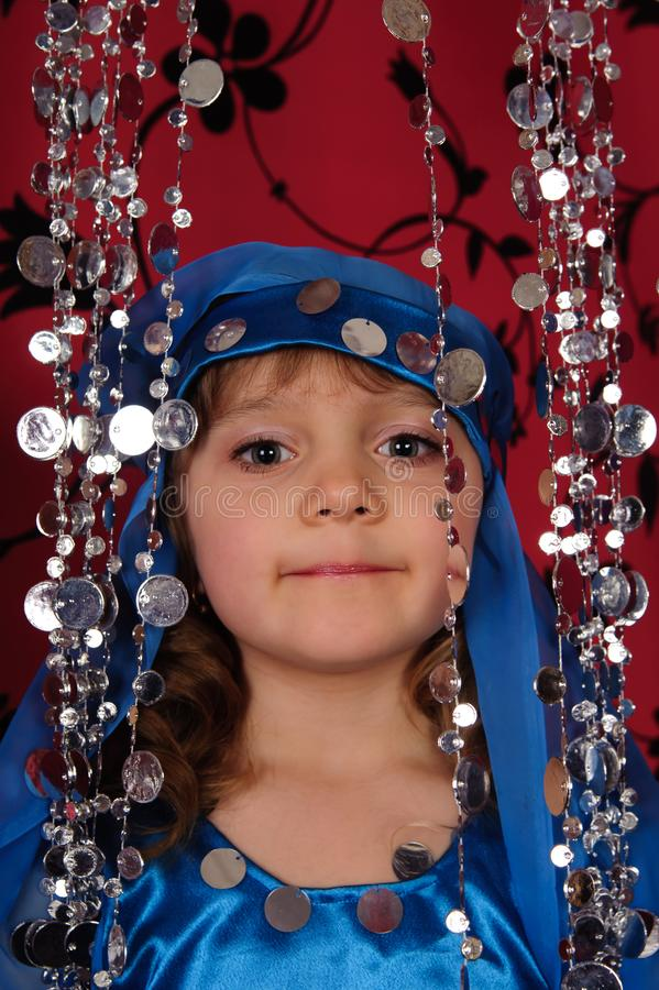 Little girl in blue oriental costume stock photography