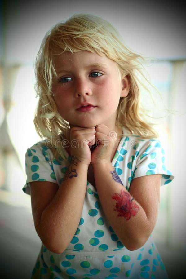 Little girl body painting. Little blond girl with flowers painted on arms stock photo