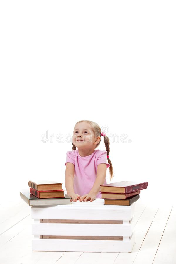 Joyful little girl with books sits on a white floor. stock photos