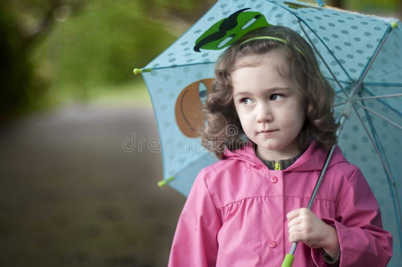 A little girl with a bored expression. A girl with a bored expression walks on a rainy day with a colorful umbrella and a pink raincoat royalty free stock image
