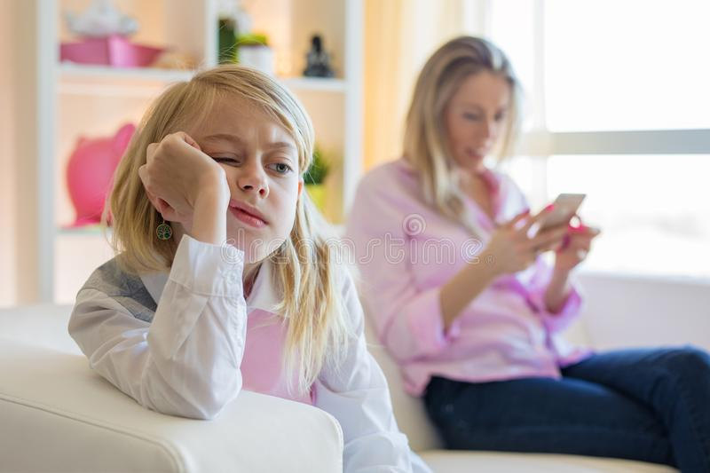 Little girl is bored while her mother is using phone royalty free stock images