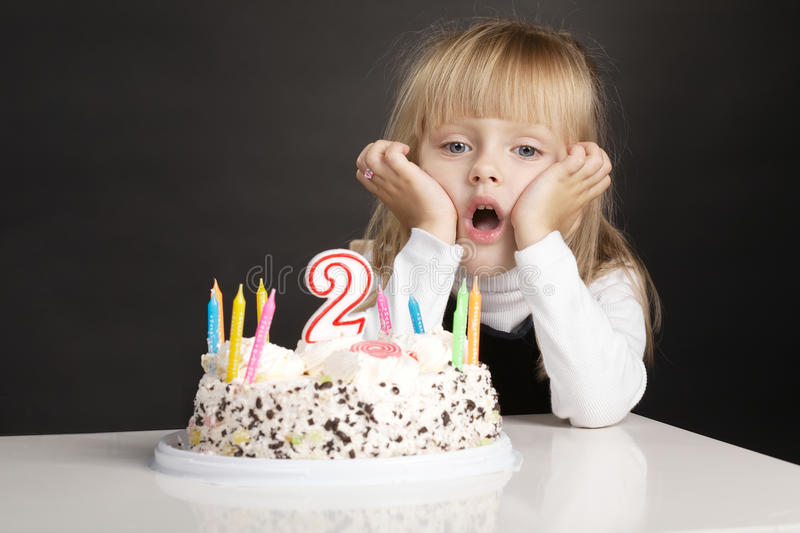 Little girl boring birthday. Photo of boring little girl with birthday cake stock photo