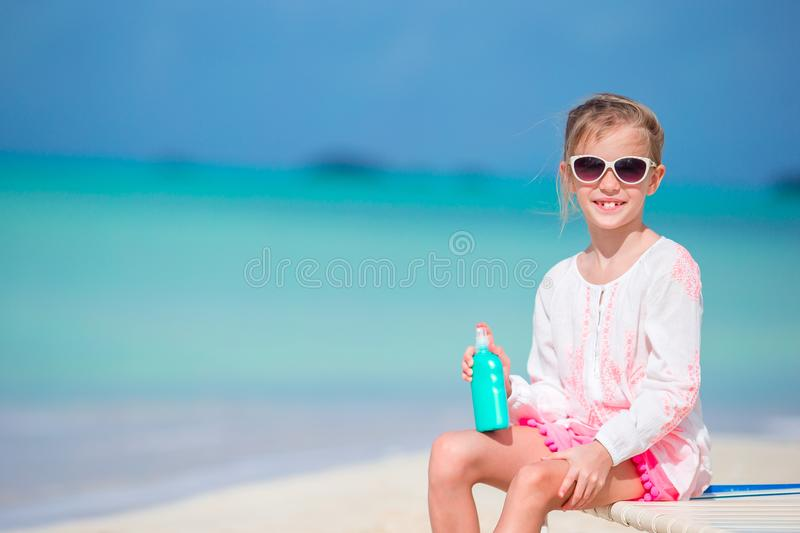Beautiful kid with bottle of sun cream on tropical beach. Little girl with bottle of sun cream sitting at tropical beach stock images
