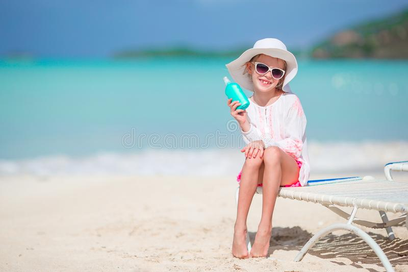 Beautiful kid with bottle of sun cream on tropical beach. Little girl with bottle of sun cream sitting at tropical beach royalty free stock photos