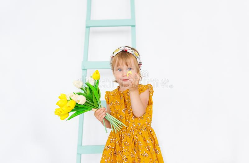 Little girl with bouquet of tulips is in a light studio with quail egg in hands. stock photo