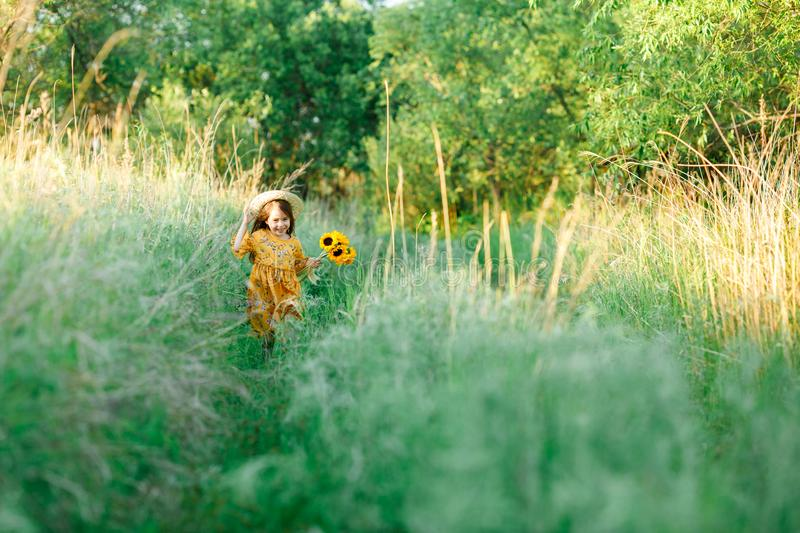 Little girl with a bouquet of wild yellow flowers run in the meadow sunny summer day in a straw hat. Copy space.  royalty free stock images