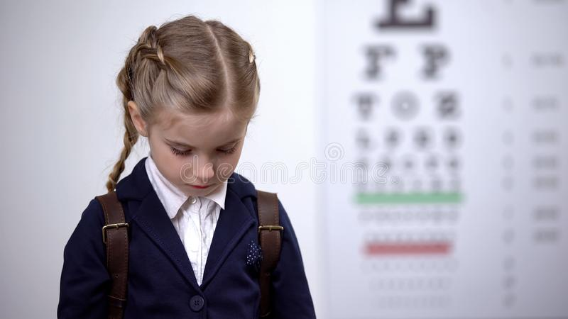 Little girl bowed her head, shy of wearing glasses to school, bullying by peers royalty free stock photography