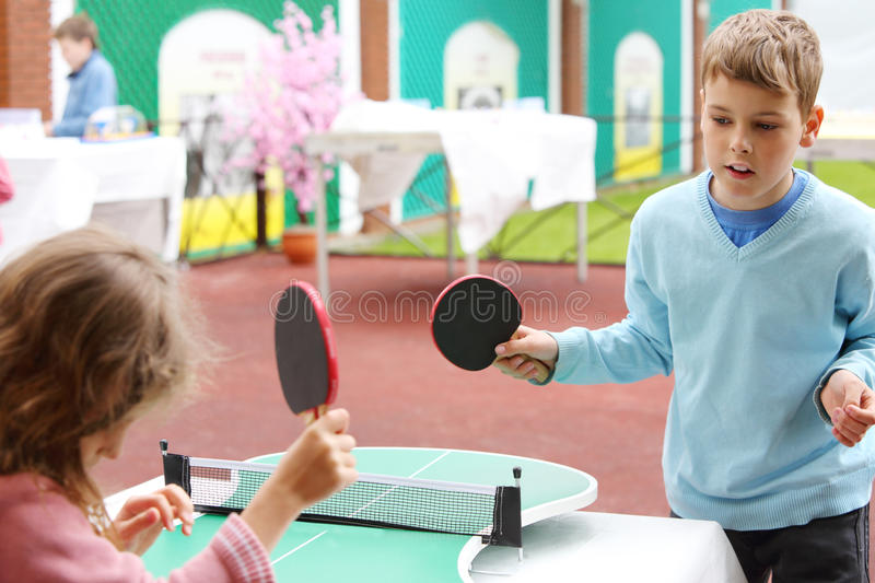 Little girl and boy in blue play table tennis in park. At summer day. Focus on boy stock photo