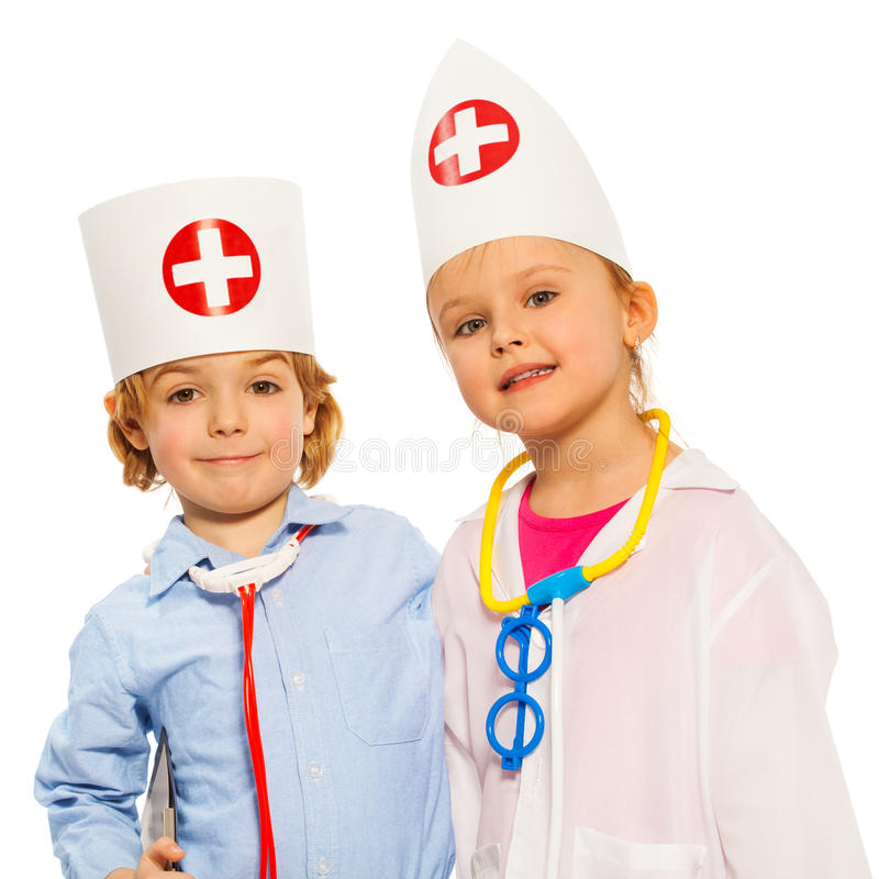 Little girl and boy in doctor costumes with caps stock photo
