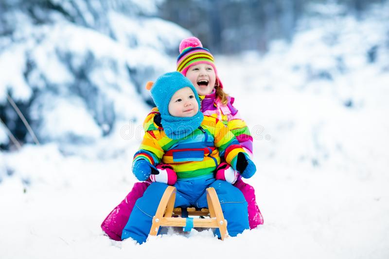 Kids on sleigh ride. Children sledding. Winter snow fun. Little girl and boy enjoy a sleigh ride. Child sledding. Toddler kid riding a sledge. Children play stock photo