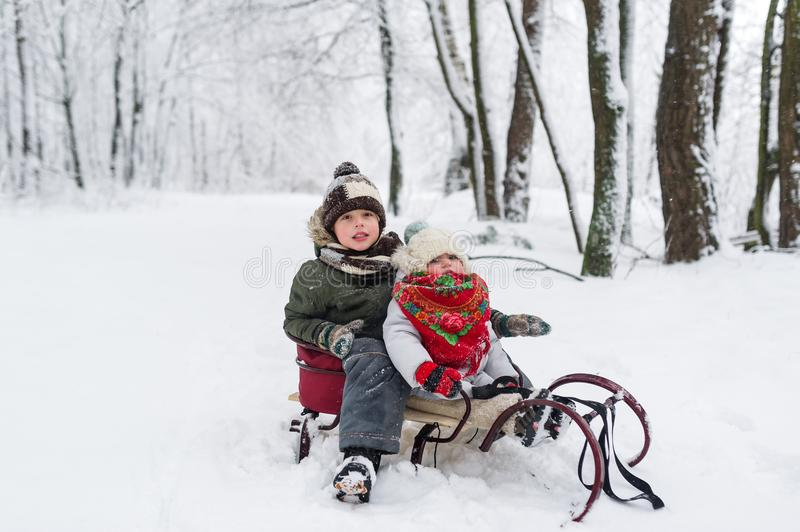 Little girl and boy enjoy a sleigh ride. Child sledding. Toddler kid riding a sledge. Children play outdoors in snow. royalty free stock images