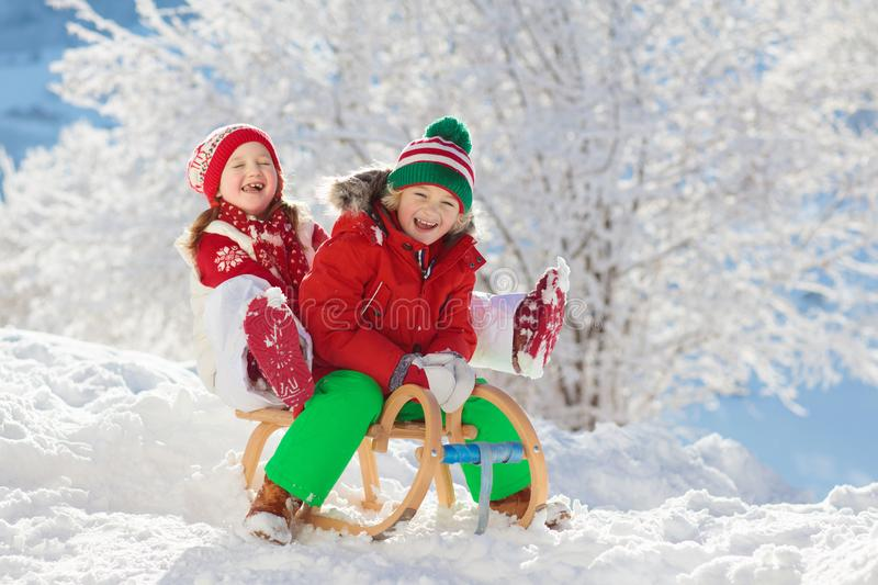 Little girl and boy enjoying sleigh ride. Child sledding. Toddler kid riding a sledge. Children play outdoors in snow. Kids sled royalty free stock photos