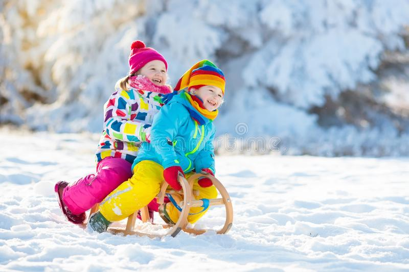 Kids play in snow. Winter sleigh ride for children. Little girl and boy enjoying sleigh ride. Child sledding. Toddler kid riding a sledge. Children play outdoors stock photos