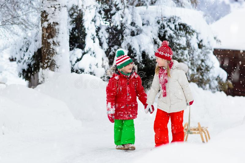 Little girl and boy enjoying sleigh ride. Child sledding. Toddler kid riding a sledge. Children play outdoors in snow. Kids sled stock image