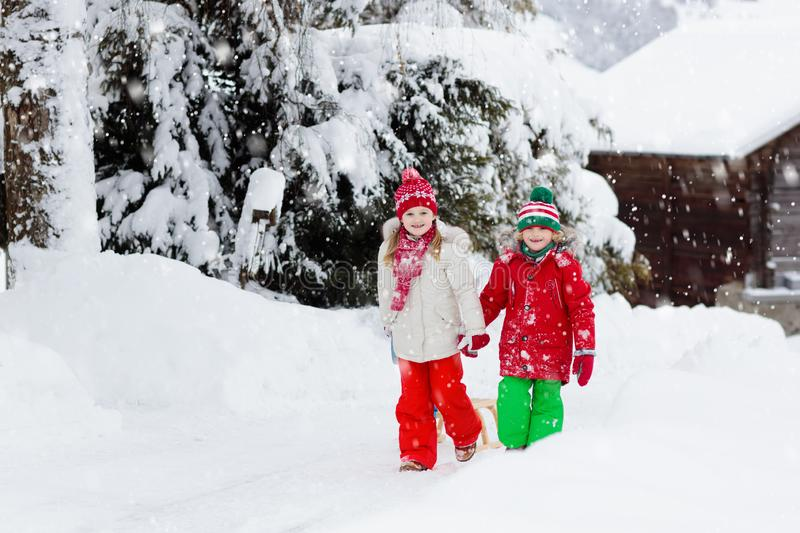 Little girl and boy enjoying sleigh ride. Child sledding. Toddler kid riding a sledge. Children play outdoors in snow. Kids sled royalty free stock photography