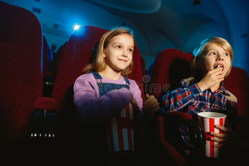 Little girl and boy watching a film at a movie theater. Little girl and boy, friends or sister and brother watching a film at a movie theater, house or cinema royalty free stock image